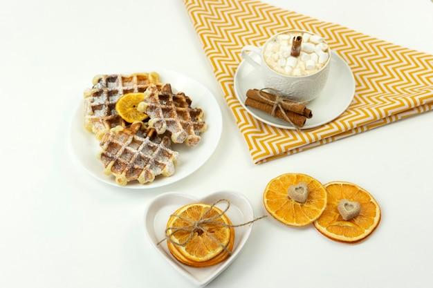 マシュマロとシナモンとベルギーワッフルのスティックを添えた早めの朝食コーヒーがテーブルの上に横たわっています