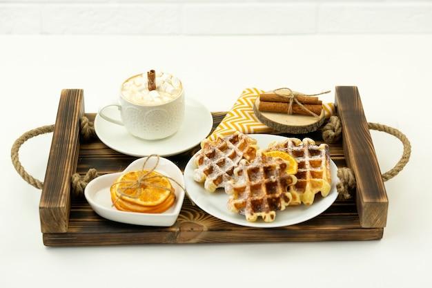マシュマロとシナモンとベルギーワッフルのスティックが付いた早めの朝食コーヒーが木製のトレイに横たわっています