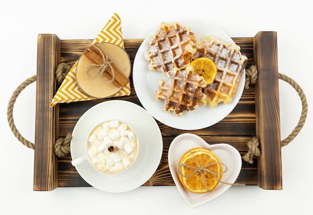 Кофе для раннего завтрака с зефиром и палочкой корицы и бельгийскими вафлями лежит на деревянном столе.