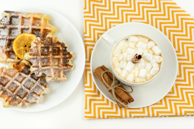 Early breakfast coffee with marshmallows and a stick of cinnamon and belgian waffles