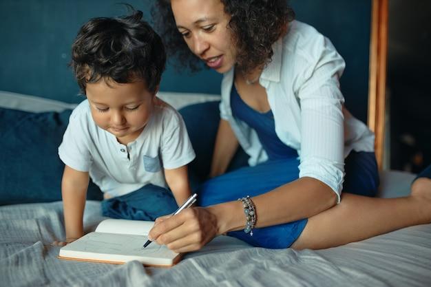 初期の発達、学習、幼年期および出産。彼女の就学前の子供と一緒にベッドに座っている思いやりのある幸せな若いヒスパニック系の母親の屋内肖像画