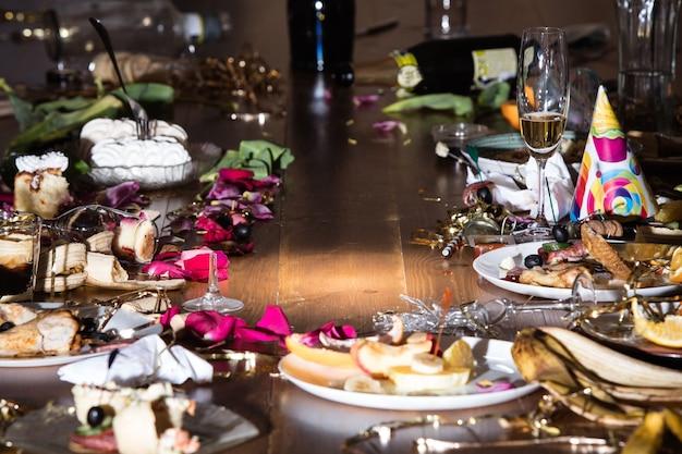 パーティー後の早朝。紙吹雪と蛇紋石、残り物、花びらが付いたテーブルの上のグラスとプレート。食べ物、飲み物、アフターパーティー、二日酔い、お祝い、ライフスタイルのコンセプト。コピースペース。