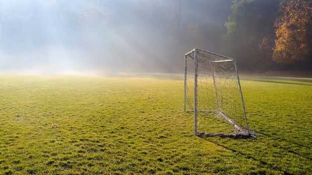 Early morning in the amateur soccer field. football game playground in autumn foggy morning.