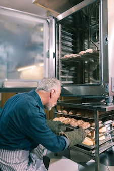Early morning. bearded owner of bakery putting croissants into oven working early in the morning