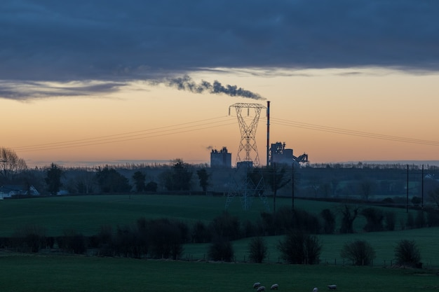 Early morning countryside landscape looking to factory in the distance with sunlight illuminating the smoke.