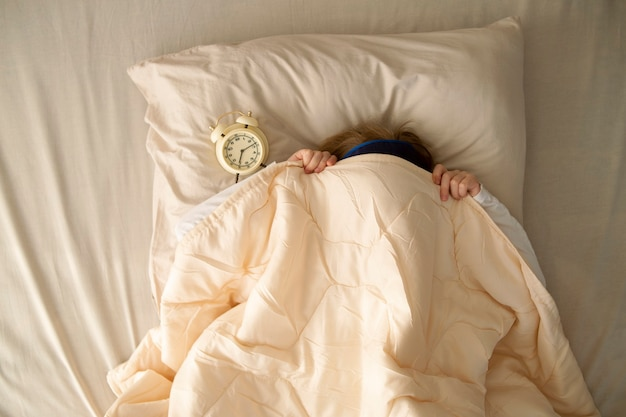 In the early morning a girl lies in bed under the covers next to the alarm clock the girl wants to sleep