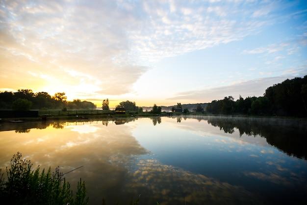 Рано утром на озере с отражением в воде