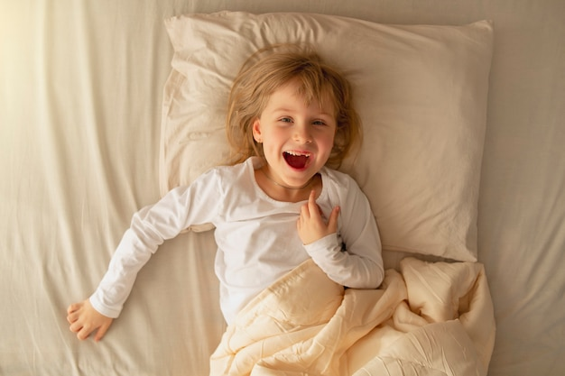 In the early morning, the preschool girl lies in bed and has fun after a good healthy sleep