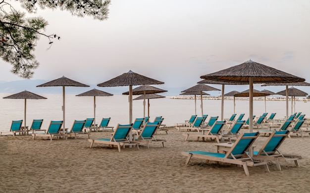 Рано утром расслабляющие кушетки с зонтиками на песчаном пляже острова тасос, греция