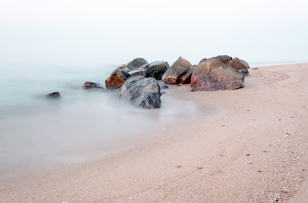 Early morning on the rocky coast of the sea. smooth water of the sea because of long exposure. time pre sunrise.