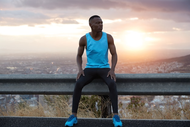 Early morning sport concept. thoughtful black ethnic man sits at traffic sign, poses against magnificent sunrise view, enjoys calm atmosphere, wears blue vest, black trousers and sportshoes.