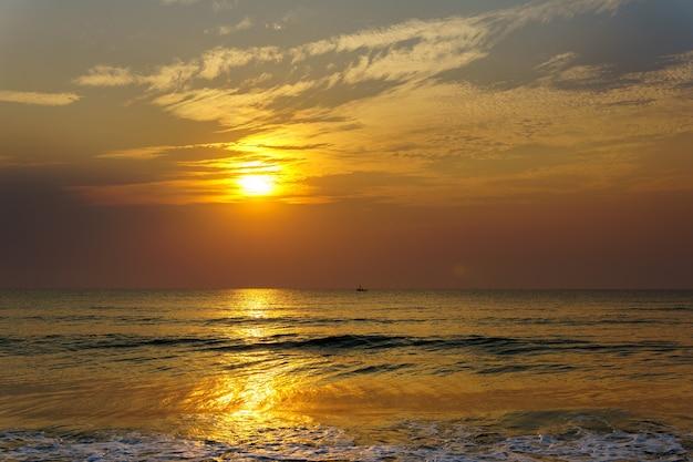 바다와 작은 낚시 보트를 통해 이른 아침 일출