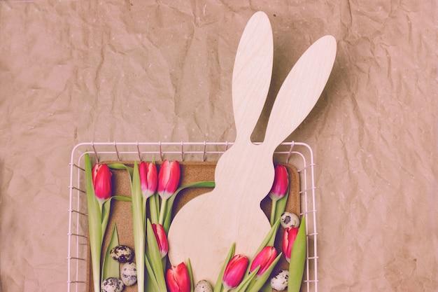 ベージュの紙の背景にウサギの形をした初期のピンクのチューリップ。ウズラの卵がうそをつく
