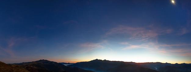 산에서 이른 새벽. 하늘에 별과 달 이을 밤 파노라마
