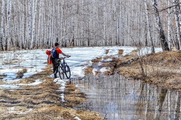 Ранней весной в лесу. путешественник идет по непроходимой лесной дороге на велосипеде.