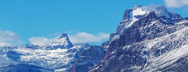 米国モンタナ州グレイシャー国立公園で最初の雪が岩や森を覆った初冬