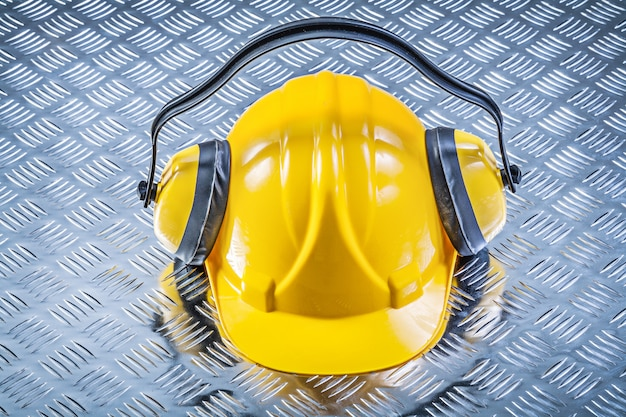 Earmuffs building helmet on grooved metal background construction concept