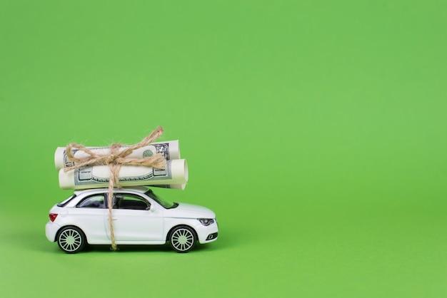 あなたの車のコンセプトで現金を稼ぎましょう。コピースペースカードと分離された明るい色の背景の上に米ドルのお金の山を巻く小さな白い車の横顔の完全な写真画像