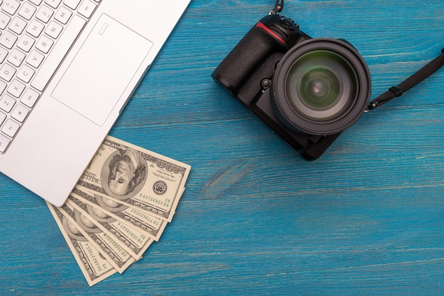 Earn money in internet dslr camera, dollars, laptop, on blue wooden background, top view
