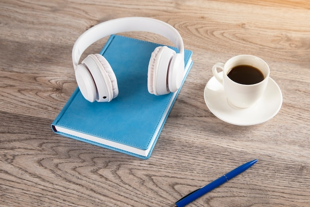 Earphone on book with coffee on wooden table