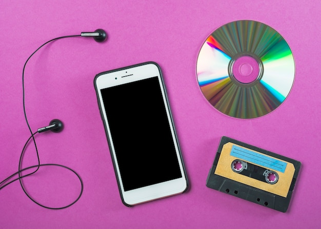 Earphone; cellphone; compact disc and cassette tape on purple background
