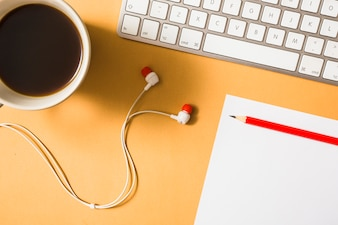 Earphone; coffee cup; keyboard; paper and red pencil on an orange background