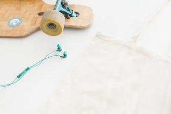 Earphone, skatingboard and handbag on white background