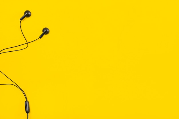 Earphone on yellow background with space for text