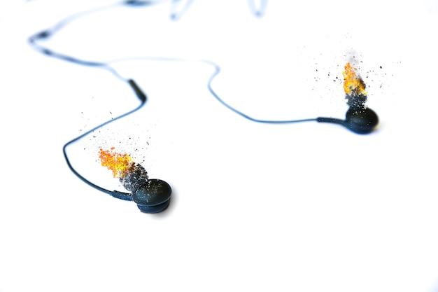白い背景の上に横たわって燃えているイヤホン。現代音楽のコンセプト。オーディオテクノロジー。