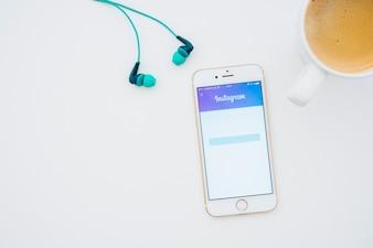 Earphones, coffee mug and phone with instagram app