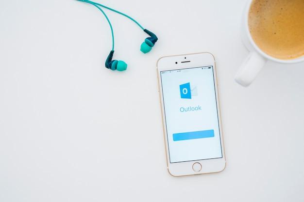 이어폰, 커피 잔 및 전망을 갖춘 전화