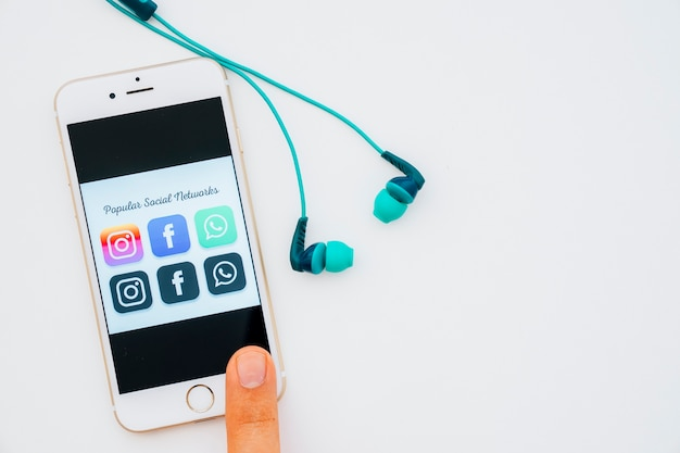 Earphones and finger touching phone with popular apps