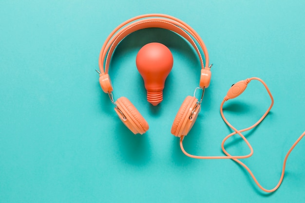 Earphones and lamp on colored surface