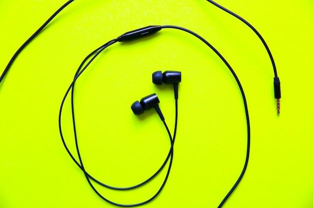 緑の背景に横たわっているイヤホン。現代音楽のコンセプト。オーディオテクノロジー。