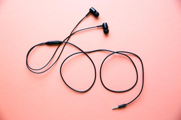 ピンクの背景に横たわっているイヤホン。現代音楽のコンセプト。オーディオテクノロジー。