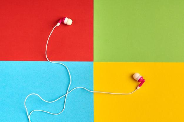 Наушники на красочном фоне известной компьютерной корпорации, логотипа производителя программного обеспечения. концепция аудио программного обеспечения. красный, зеленый, синий, желтый цвета бумаги. логотип корпорации.