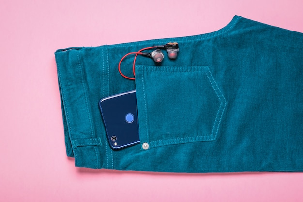Earphones and phone in pocket of jeans on pink surface