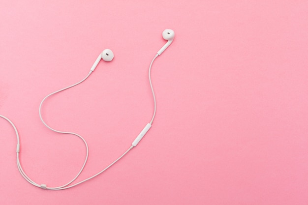 Earphones on pink surface