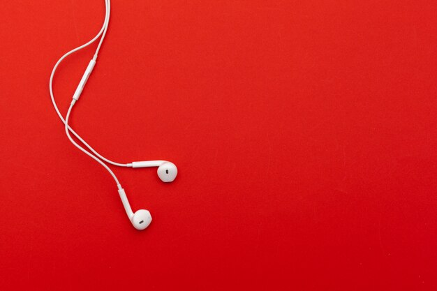 Earphones on red surface