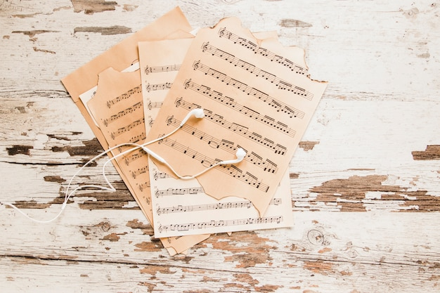 Earphones and sheet music on crumbling tabletop