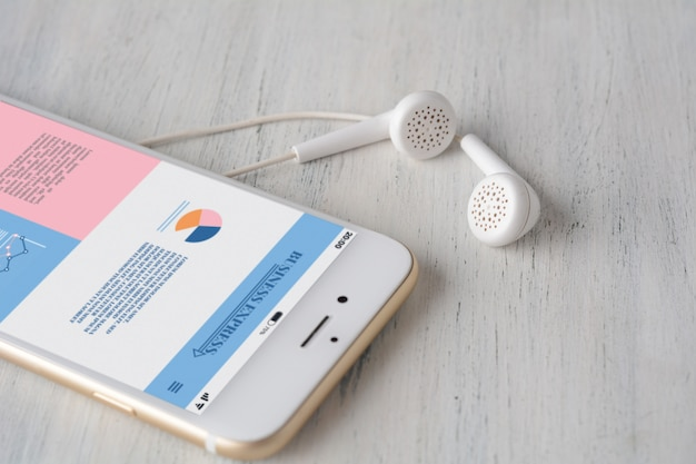 Earphones and smartphone with statistics about company growth
