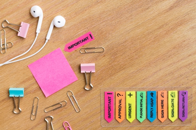 Earphones with stationery located on wooden table
