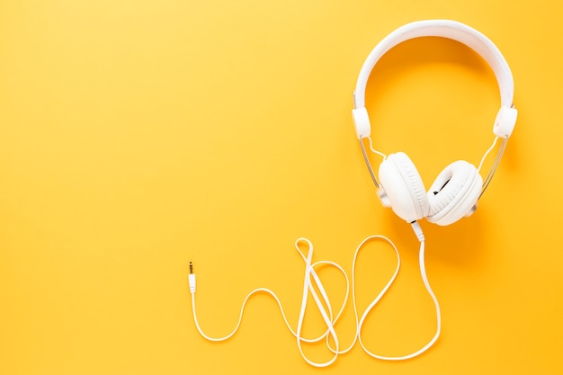 Earphones on yellow background with copy space