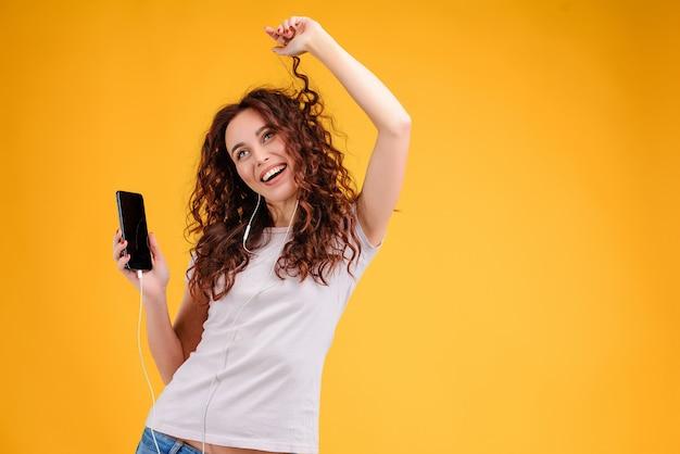 黄色の背景に分離されたearpodsから音楽の音に合わせて踊る女性