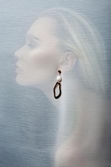 透明な生地に挿入された女性の耳のイヤリング
