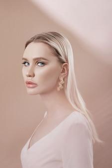투명 컬러 패브릭을 통해 섹시한 금발 여자의 귀에 귀걸이와 보석.