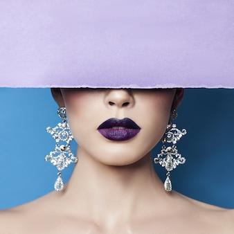 섹시한 여자의 귀에 귀걸이와 보석은 보라색 종이에 눌렀습니다. 완벽한 갈색 머리 소녀, 화려한 신비로운 모습. 보석 광고, 여자 귀에 아름다운 귀걸이.