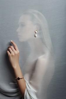 透明な生地に挿入されたセクシーな女性の耳のイヤリングとジュエリー。完璧なブロンドの女の子、ゴージャスな神秘的な外観。広告ジュエリー、女の子の耳の美しいイヤリング