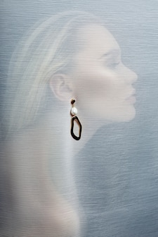 Earrings and jewelry in the ear of a sexy woman inserted through a transparent fabric