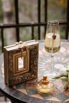 Earrings lie on the golden frame, perfume stand on the table with a glass of champagne.